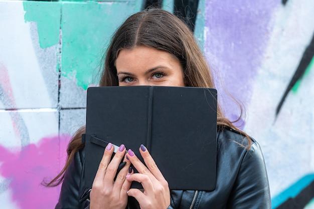 Una giovane donna civettuola con un fiocco nero tra le mani appoggiata a un muro spruzzato di graffiti