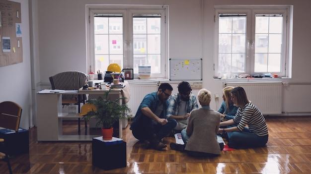 Giovani concentrati laboriosi imprenditori creativi seduti sul pavimento dell'ufficio nel cerchio e il brainstorming. il lavoro di squadra e il concetto di solidarietà.
