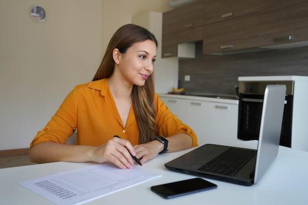 Giovane donna concentrata che lavora compilando documenti da casa