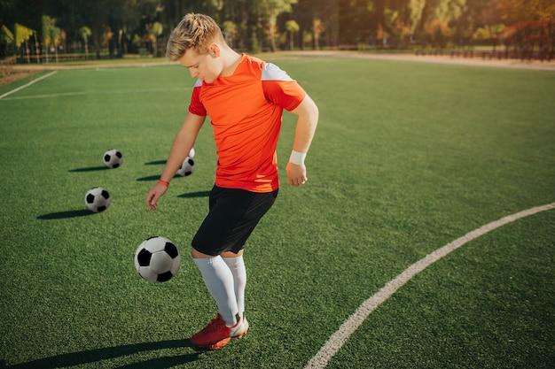 Giovane giocatore di football americano che si esercita sul prato inglese. calcia la palla con una gamba. guy è concentrato. il sole estivo è fuori.