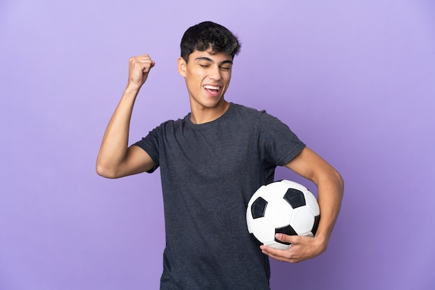 Uomo del giovane giocatore di football americano sopra la parete viola isolata che celebra una vittoria