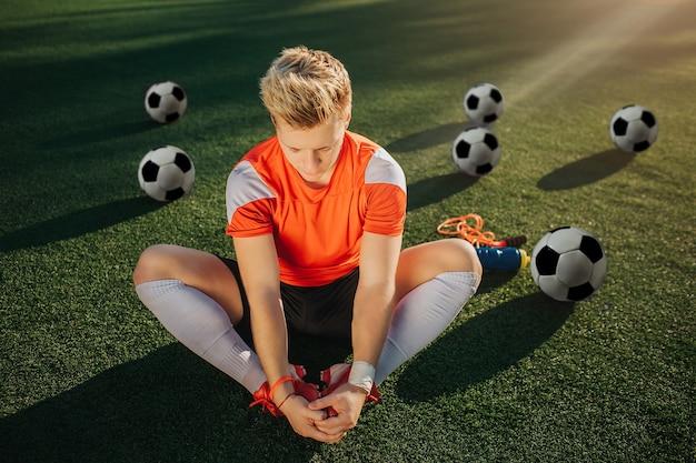 Giovane calciatore seduto sul prato e che si estende