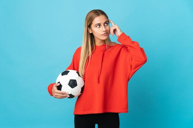 Donna giovane calciatore sull'azzurro che ha dubbi e pensiero