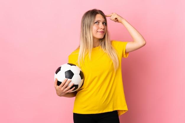 Giovane donna del giocatore di football americano isolata sulla parete rosa che ha dubbi con l'espressione confusa del fronte