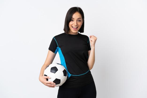 Giovane donna del giocatore di football americano isolata su bianco che celebra una vittoria nella posizione del vincitore