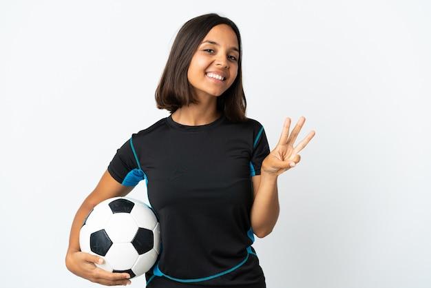 Donna giovane calciatore isolata su bianco felice e contando tre con le dita