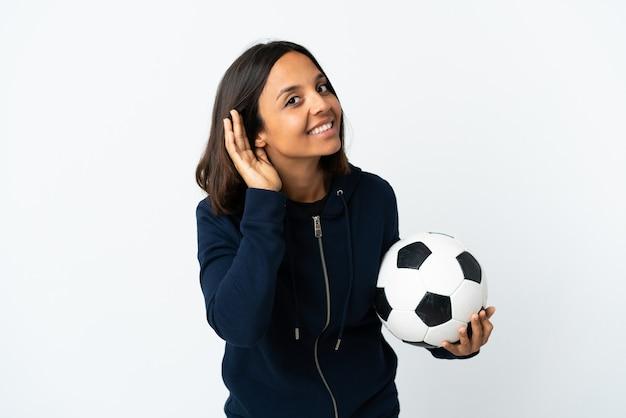 Donna giovane calciatore isolata su bianco ascoltando qualcosa mettendo la mano sull'orecchio