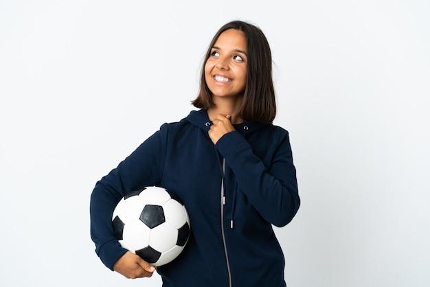 Donna giovane giocatore di football americano isolata su bianco che osserva in su mentre sorride