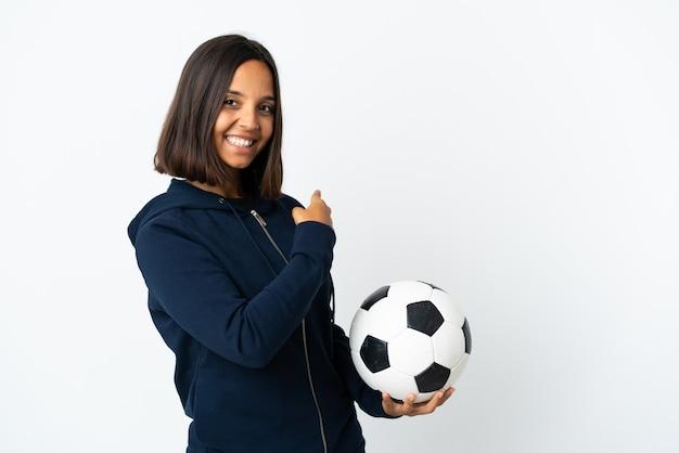 Giovane donna del giocatore di football americano isolata su bianco che indica indietro