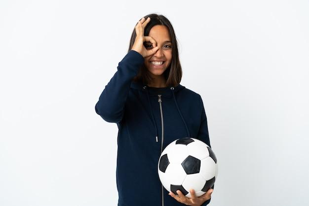 Donna giovane calciatore isolata su bianco che mostra segno giusto con le dita