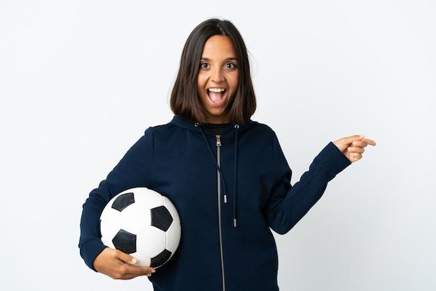Donna giovane calciatore isolata su bianco sorpreso e puntando il dito a lato