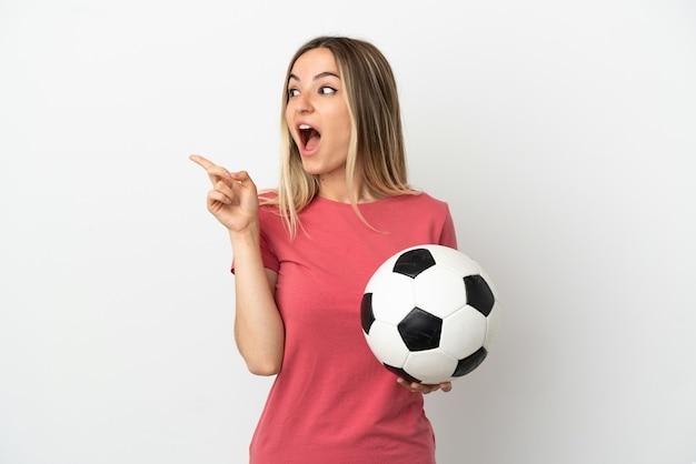 La giovane donna del giocatore di football americano sopra la parete bianca isolata intende realizzare la soluzione mentre alza un dito su