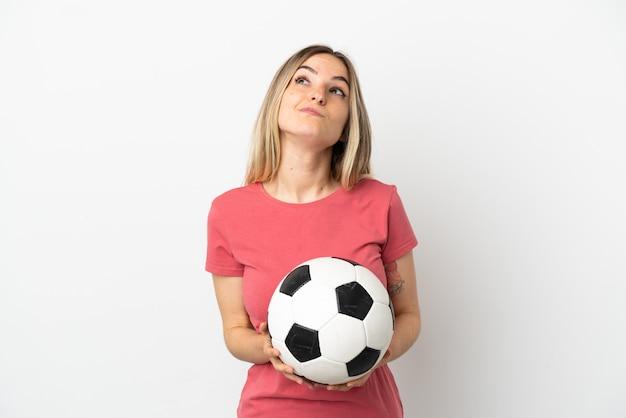 Giovane donna del giocatore di football americano sopra il muro bianco isolato e alzando lo sguardo