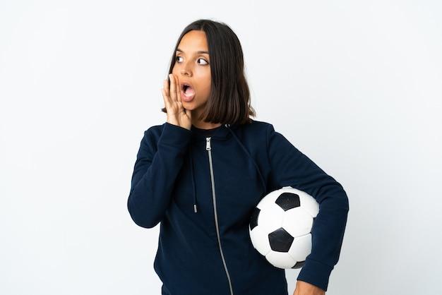 Donna giovane calciatore isolata su bianco che bisbiglia qualcosa con gesto di sorpresa mentre guarda al lato