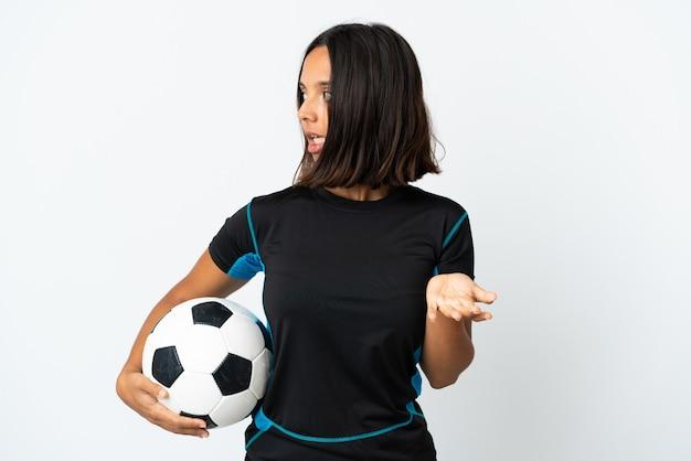 Donna giovane calciatore isolata su bianco con espressione di sorpresa mentre guarda di lato