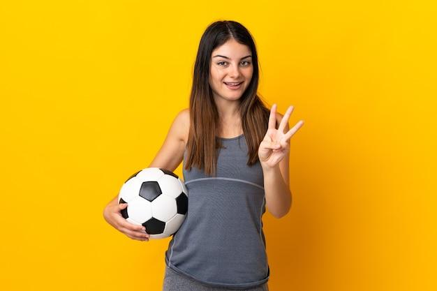 Donna giovane calciatore isolata su giallo felice e contando tre con le dita