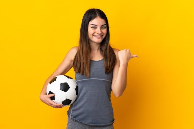 Donna giovane calciatore isolata su giallo che punta di lato per presentare un prodotto