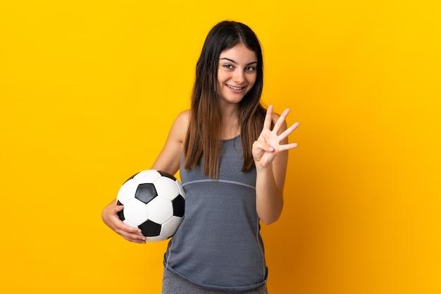 Donna giovane calciatore isolata sulla parete gialla felice e contando quattro con le dita