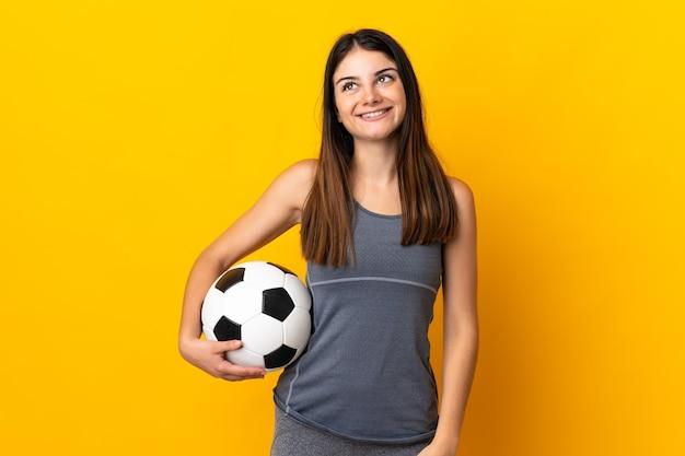 Giovane donna del giocatore di calcio isolata sulla parete gialla che pensa un'idea mentre osserva in su