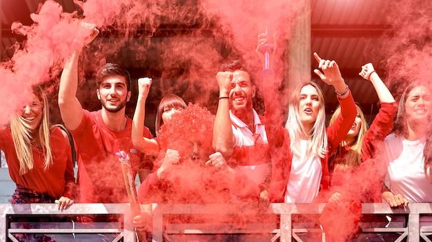 Giovani tifosi del tifoso che incoraggiano con il fumo colorato che guardano la partita di calcio insieme allo stadio