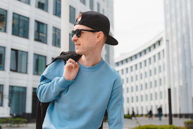 Giovane ragazzo hipster alla moda bello libero che cammina per strada, indossando un cappello da sole