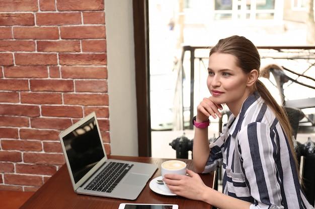Giovane libero professionista che beve caffè mentre lavora al computer portatile nella caffetteria