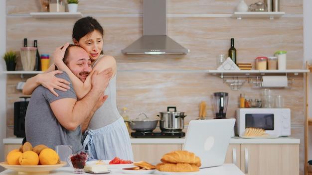 Il giovane libero professionista legge buone notizie mentre fa colazione e lavora al computer portatile in cucina. imprenditore euforico di successo felicissimo a casa al mattino, vincitore e trionfo degli affari