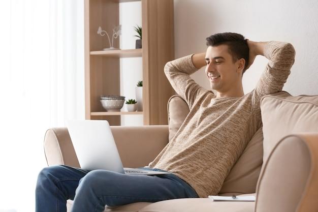 Giovane libero professionista con laptop che si rilassa sul divano di casa