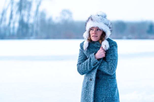 Giovane donna di congelamento sullo spazio della copia dell'insegna del lago ghiacciato di inverno