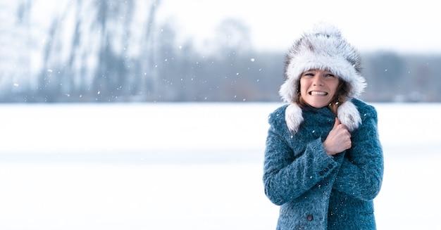 Giovane donna di congelamento sul lago ghiacciato di inverno. banner.