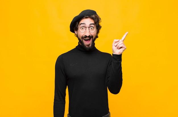 Giovane artista francese che si sente come un genio felice ed eccitato dopo aver realizzato un'idea, alzando allegramente il dito, eureka! contro il muro arancione