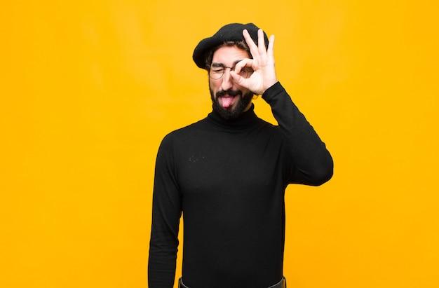 Uomo giovane artista francese che sorride felicemente con la faccia buffa, scherzando e guardando attraverso lo spioncino