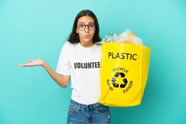 Giovane ragazza francese che tiene un sacco pieno di bottiglie di plastica da riciclare avendo dubbi mentre si alzano le mani