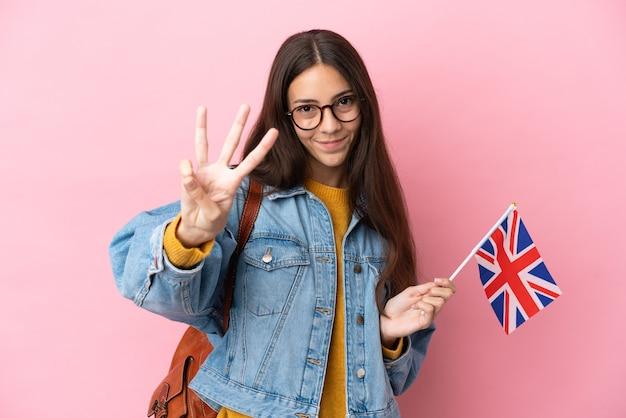 Giovane ragazza francese in possesso di una bandiera del regno unito isolata su sfondo rosa felice e contando tre con le dita