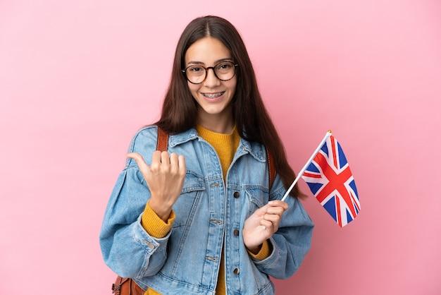 Giovane ragazza francese con una bandiera del regno unito isolata su sfondo rosa che punta di lato per presentare un prodotto