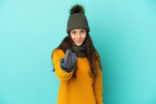 Giovane ragazza francese isolata su sfondo blu con cappello invernale che invita a venire con la mano. felice che tu sia venuto