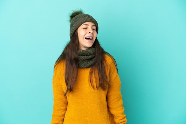 Giovane ragazza francese isolata su sfondo blu con cappello invernale che ride