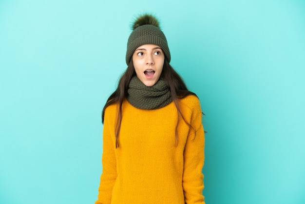 Giovane ragazza francese isolata su sfondo blu con cappello invernale che guarda in alto e con espressione sorpresa