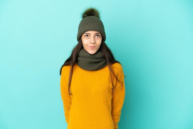 Giovane ragazza francese isolata su sfondo blu con cappello invernale e alzando lo sguardo