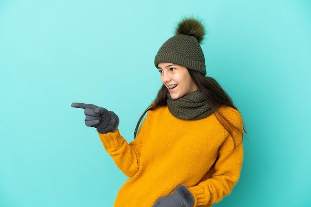 Giovane ragazza francese isolata su sfondo blu con cappello invernale che punta il dito di lato e presenta un prodotto