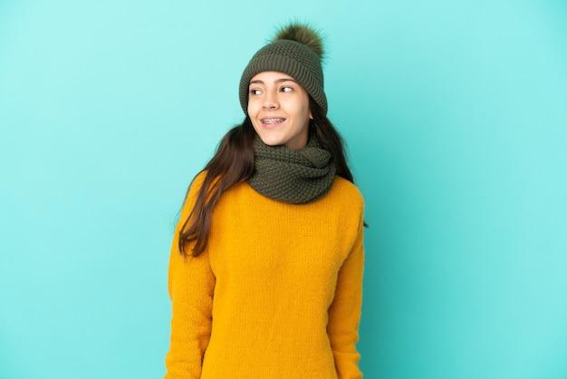 Giovane ragazza francese isolata su sfondo blu con cappello invernale che pensa a un'idea mentre guarda in alto