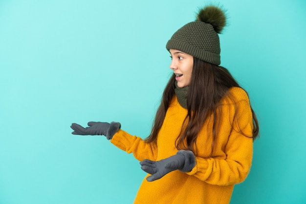 Giovane ragazza francese isolata su sfondo blu con cappello invernale con espressione di sorpresa mentre guarda di lato