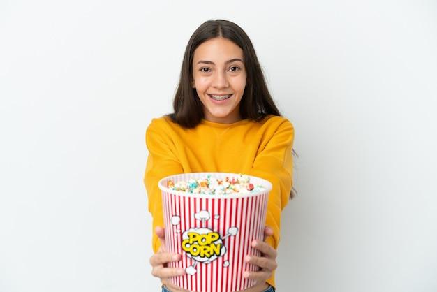 Giovane ragazza francese isolata su sfondo bianco con in mano un grande secchio di popcorn