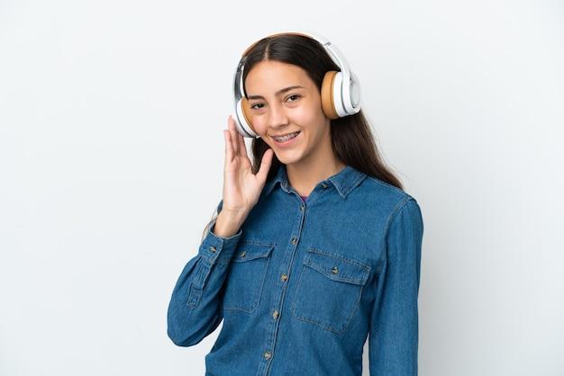 Giovane ragazza francese isolata su sfondo bianco ascoltando musica