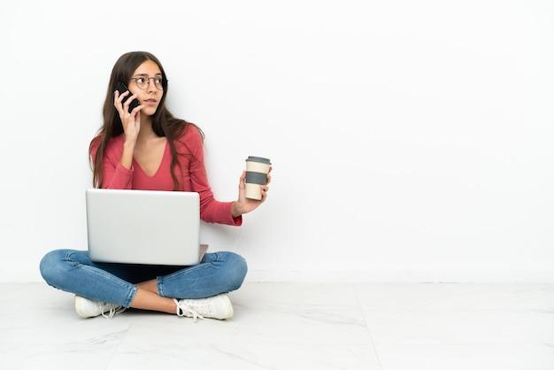 Giovane ragazza francese seduta sul pavimento con il suo computer portatile che tiene il caffè da portare via e un cellulare