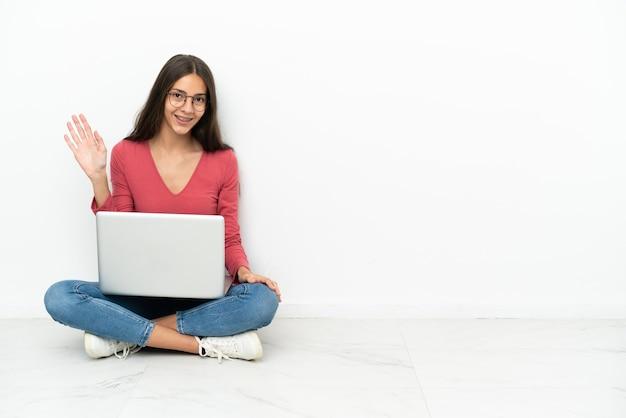 Giovane ragazza francese seduta sul pavimento con il suo laptop salutando con la mano con felice espressione