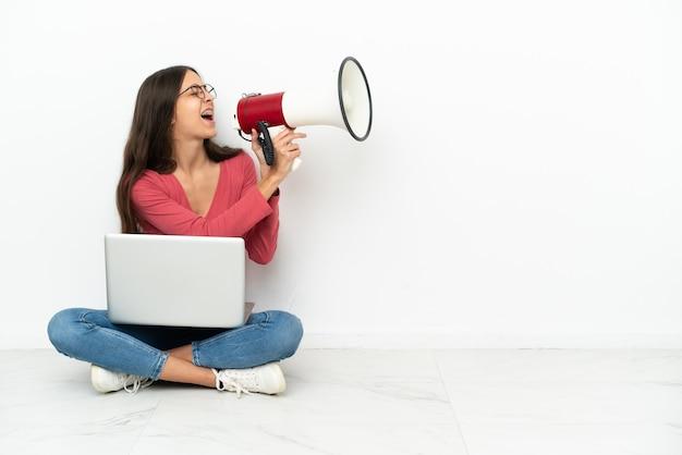 Giovane ragazza francese seduta sul pavimento con il suo laptop che grida attraverso un megafono