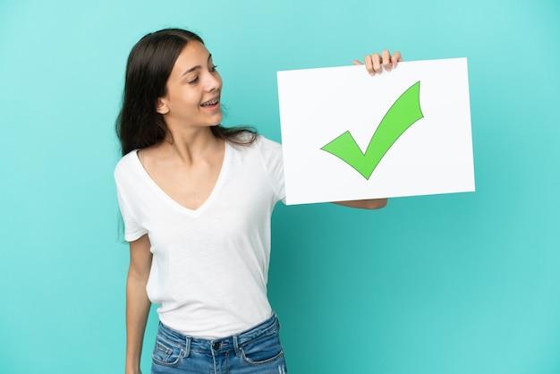 Giovane donna francese isolata su sfondo blu in possesso di un cartello con testo icona del segno di spunta verde con espressione felice