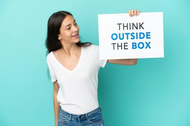 Giovane donna francese isolata su sfondo blu in possesso di un cartello con testo think outside the box