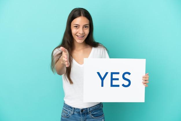 Giovane donna francese isolata su priorità bassa blu che tiene un cartello con il testo sì facendo un affare